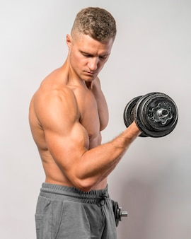 Side view of shirtless fit man posing while holding weights
