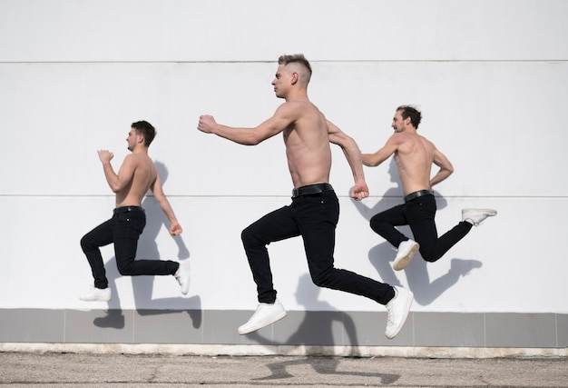 Side view of shirtless hip hop dancers in mid-air