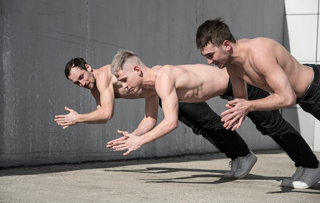Side view of shirtless hip hop dancers rehearsing outside