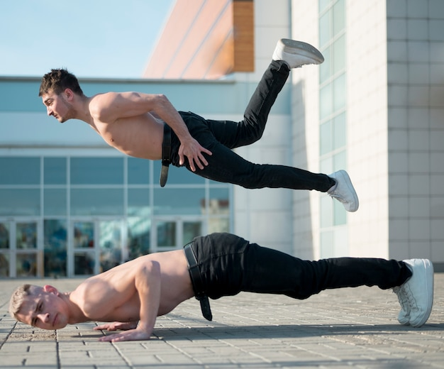 Side view of shirtless hip hop performers dancing