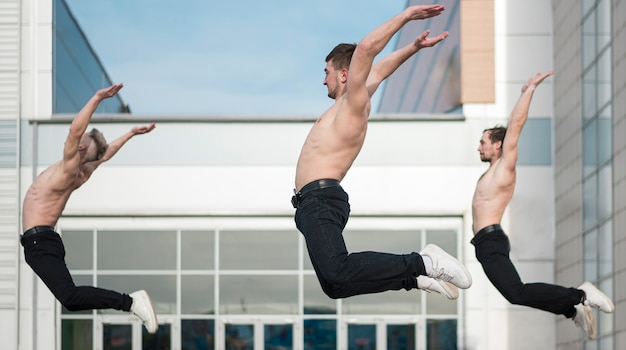 Side view of shirtless hip hop performers posing mid-air
