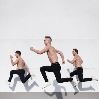 Side view of shirtless hip hop performers posing while dancing