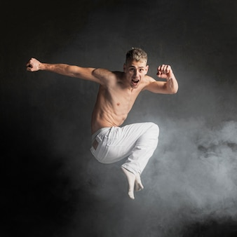 Side view of shirtless male dancer posing in mid-air
