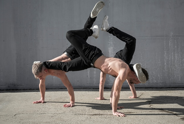 Side view of shirtless male hip hop dancers rehearsing together outside