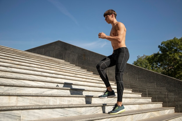 Side view of shirtless man exercising on stairs outdoors