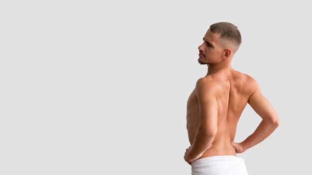 Vista laterale dell'uomo senza camicia che posa con lo spazio della copia