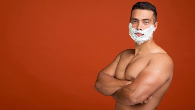 Side view of shirtless man posing with shaving cream on his face