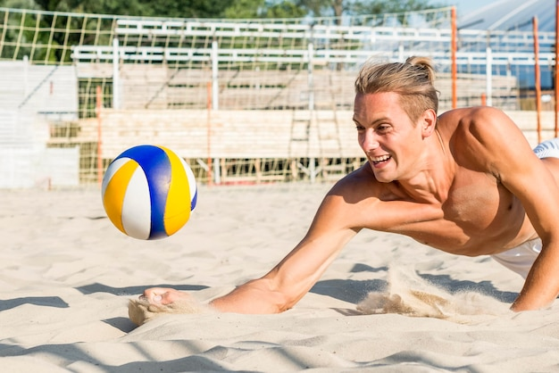 Side view of shirtless man reaching to hit volleyball before it hits the sand
