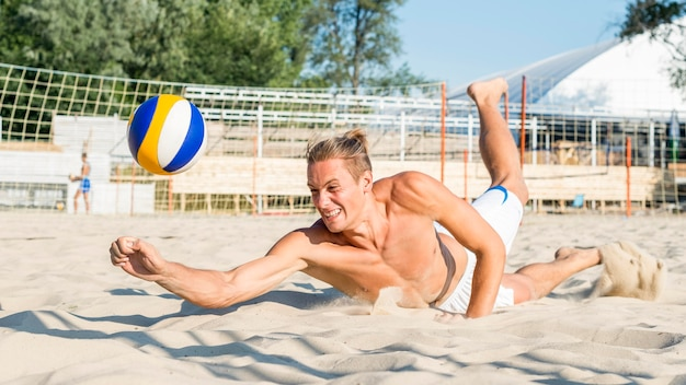 Side view of shirtless man reaching to hit volleyball