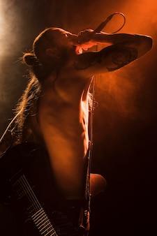 Вид сбоку мужчина без рубашки поет на сцене
