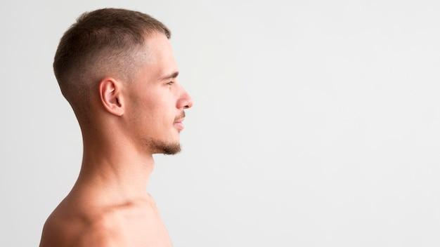 Vista laterale dell'uomo senza camicia con lo spazio della copia