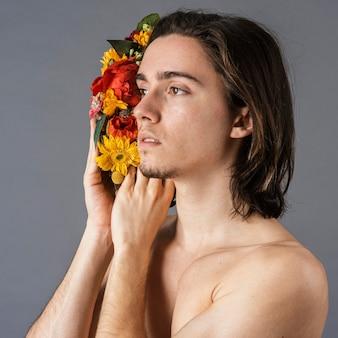 Vista laterale dell'uomo senza camicia con corona di fiori