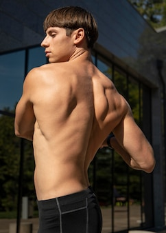 Side view of shirtless man working out outdoors