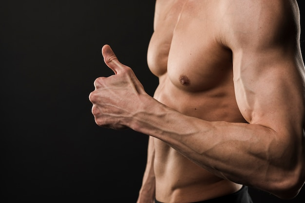 Side view of shirtless muscled man giving thumbs up