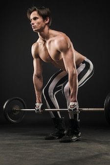 Side view of shirtless muscled man lifting weights
