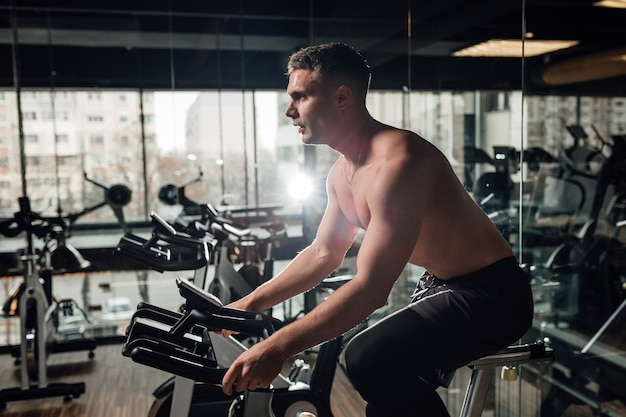 Side view of shirtless young guy exercising on bike near mirror in modern gym