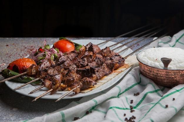 Вид сбоку шашлык на шпажках с помидорами и луком и айран в белой тарелке