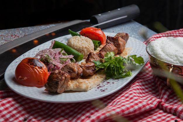 Vista laterale shish kebab con verdure fritte e cipolla tritata e ayran e coltello nel piatto bianco