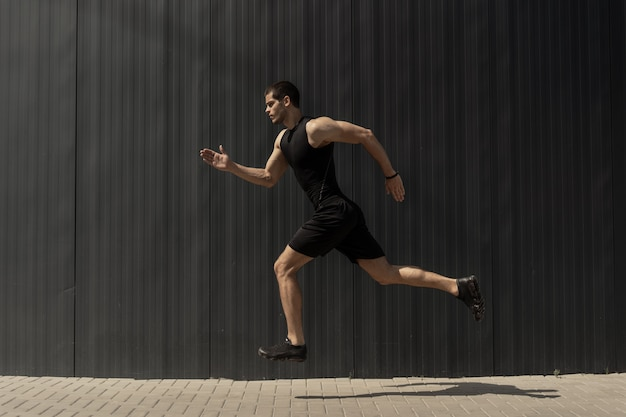 Side view shot of a fit young, athletic man jumping and running.