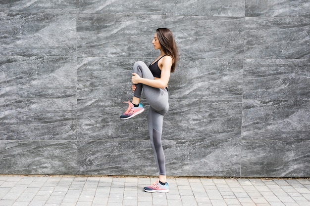 Side view shot of fit young woman doing cardio interval training against grey wall.