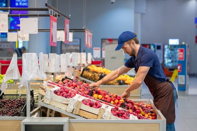 新鮮な果物を設定する店で働くエプロンを身に着けている男の側面写真