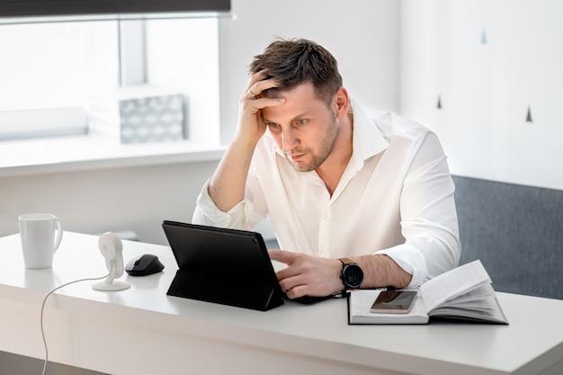 物思いにふける若者が自宅で座っているとラップトップに取り組んでの側面図ショット。ホームオフィスから働いている白人男性。