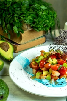 Side view of shrimp salad with avocado and cherry tomatoes in bowl