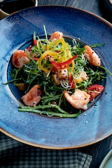 Side view of shrimp salad with bell peppers and arugula on a plate