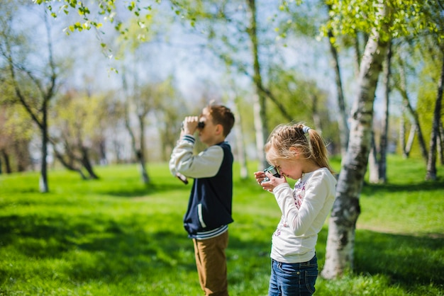 Side view of siblings with camera and binoculars