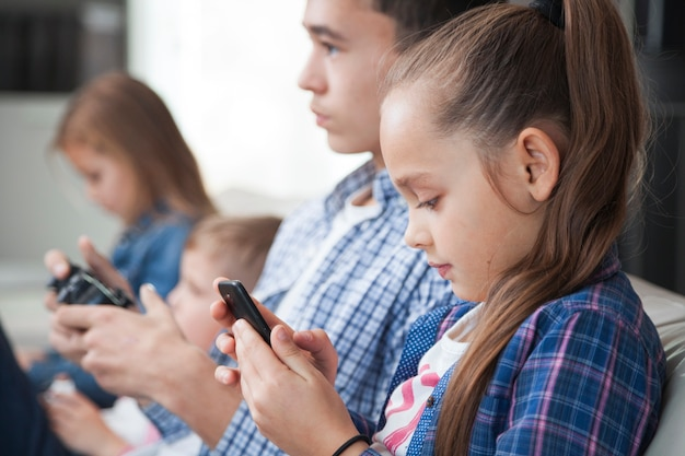 Side view siblings with smartphone and controller