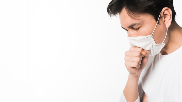 Side view of sick man with medical mask coughing