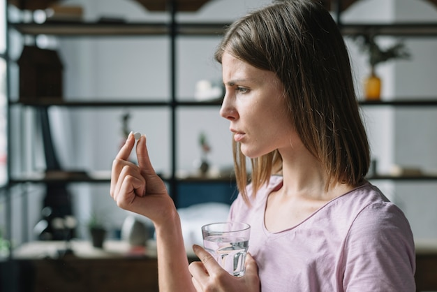 Side view of a sick young woman looking at pill