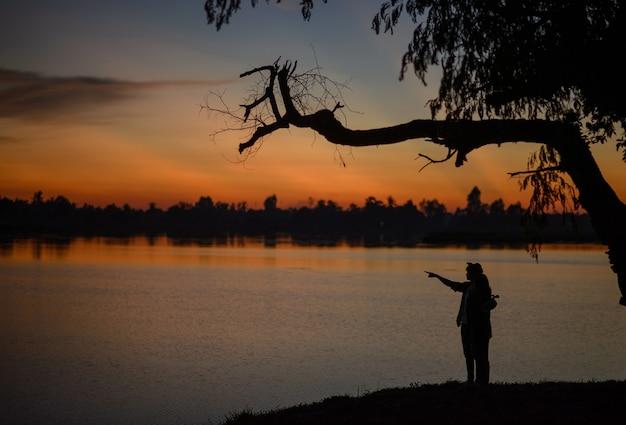황혼의 호수 근처에 서 있는 젊은 부부의 측면 실루엣, 연인은 푸른 시간에 일몰과 함께 낭만적인 순간을 가지고 있습니다