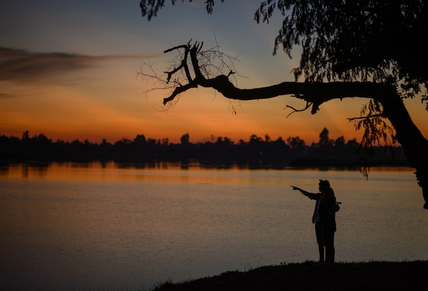 Side view silhouette of a young couple standing near the lake with twilight, the lover have romantic moment with sunset in blue hour