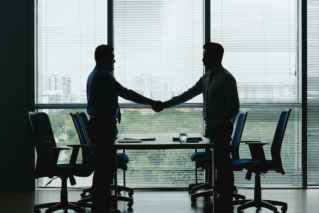 Side view of silhouettes of two unrecognizable men shaking hands in the office