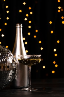 Side view silver bottle with champagne and party globe