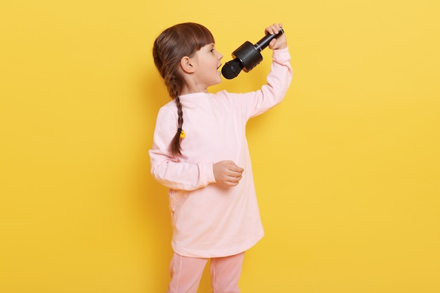 Side view of singing little girl wearing pale pink attire and having pigtails hairstyle, child holding microphone and performing against yellow wall.