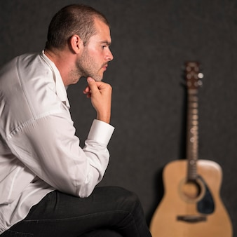Side view sitting man and blurred acoustic guitar