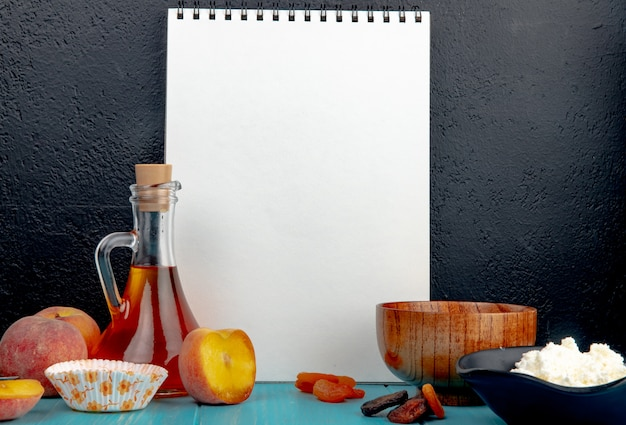 Side view of a sketchbook and fresh ripe peaches dried apricots cottage cheese and olive oil in a glass bottle on black