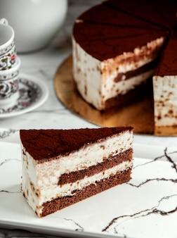 Side view of slice of tiramisu cake on plate