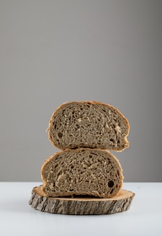 Side view sliced bread on wood on white surface. vertical space for text