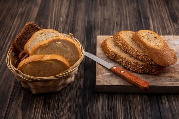 Vista laterale della pannocchia con semi marrone di fette di pane con il coltello sul tagliere e quelli bianchi di segale nel cestino su fondo di legno