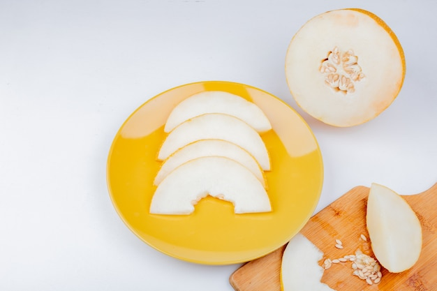 Side view of sliced melon and seeds in plate and on cutting board with cut one on white background