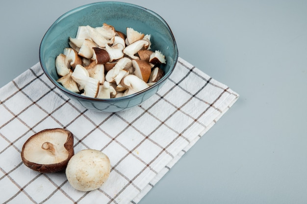 Side view of sliced mushrooms in a bowl on plaid napkin on light blue