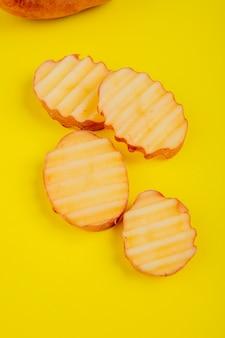 Vista laterale della patata rossa affettata su superficie gialla