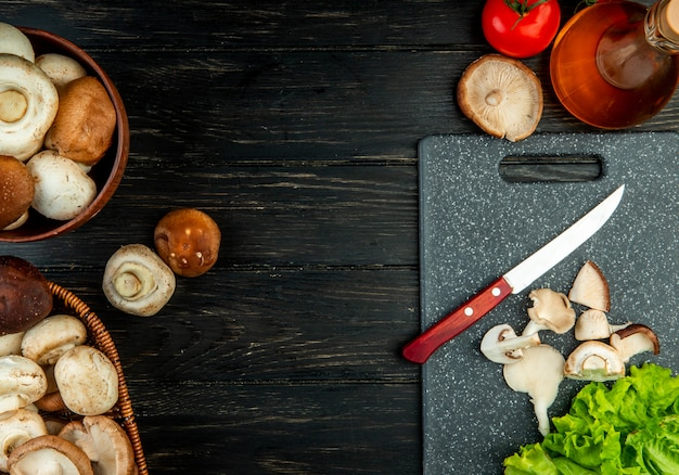 Side view of sliced and whole mushrooms with kitchen knife on a black cutting board on black wood with copy space