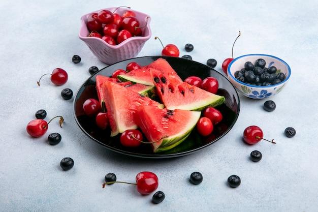 Fette di vista laterale di anguria su un piatto con mirtilli e ciliegie