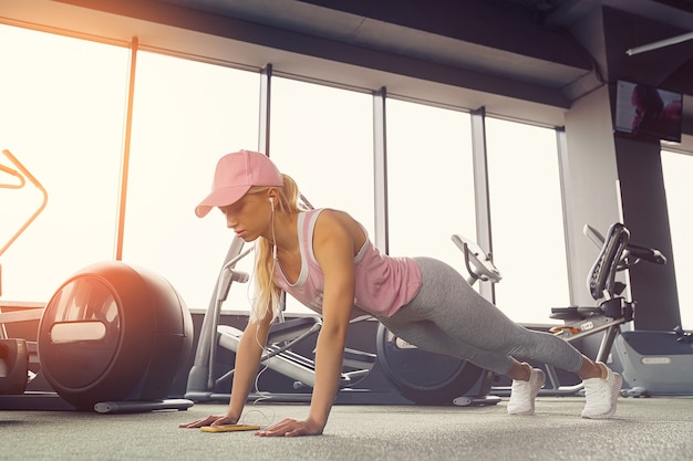 Side view of a slim fitness young blonde girl doing planking exercise