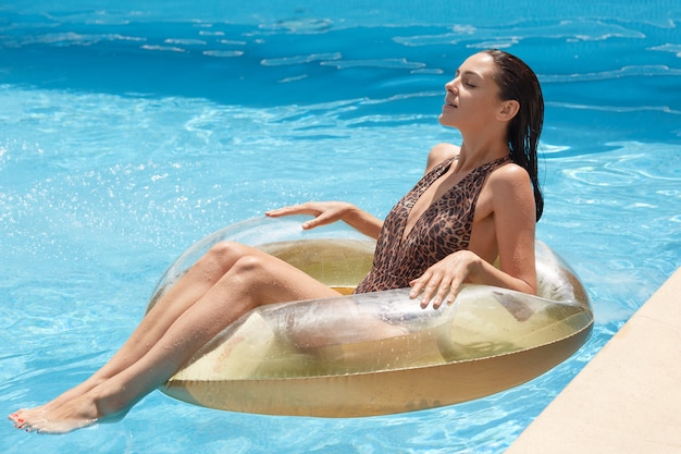 Side view of slim tanned woman in swimming suit with leopard print, looks while lying on inflatable ring in swimming pool, spending hot summer days at luxury resort. recreation and vacation concept.