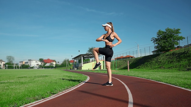 Side view of slim woman practicing high knees exercise before running at stadium. stunning fit girl wearing black sportswear and white cap training in summer sunny day, warming up. sport concept.